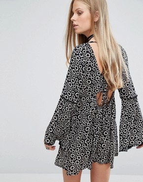 photo Swing Dress with Flared Sleeves and Tie Back In Daisy Chain Print by Kiss The Sky, color Black - Image 1